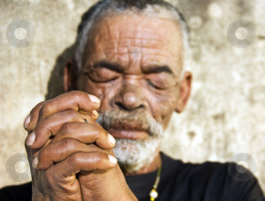 An old African man with folded hands - focus on the weathered hands